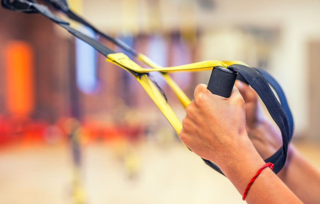 TRX. Female hands with fitness TRX straps in gym.