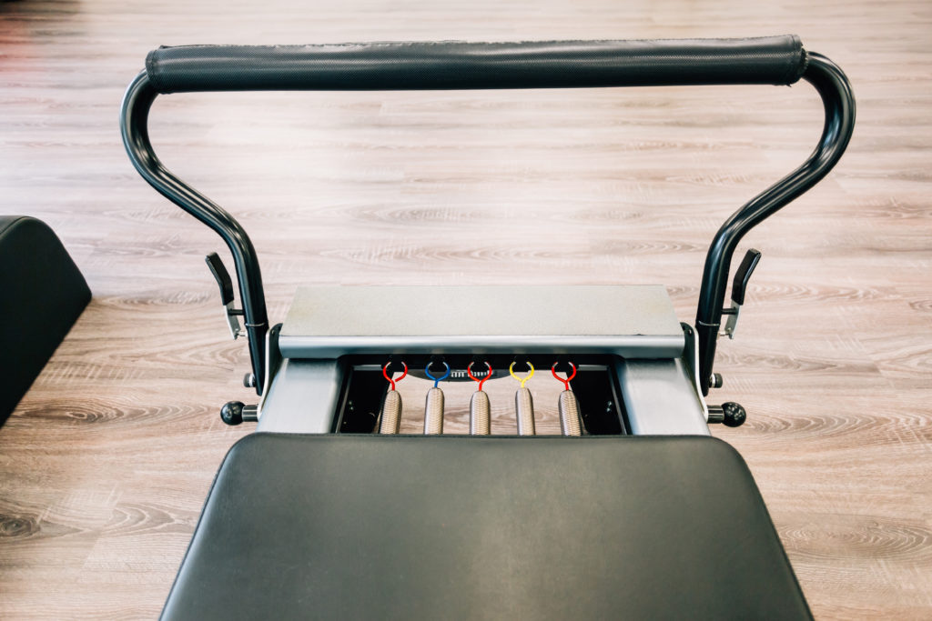 Pilates reformer close-up with focus on colored springs.